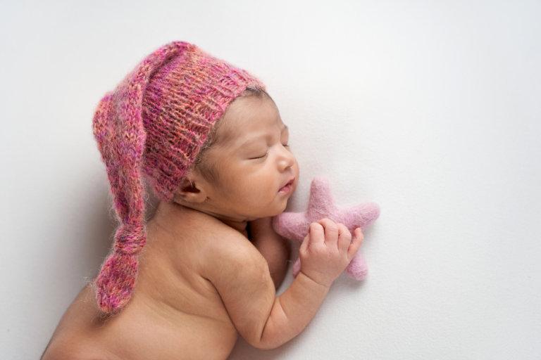 Newborn baby photo with plush starfish with soft sleeping cap for girl in Philadelphia, Pennsylvania