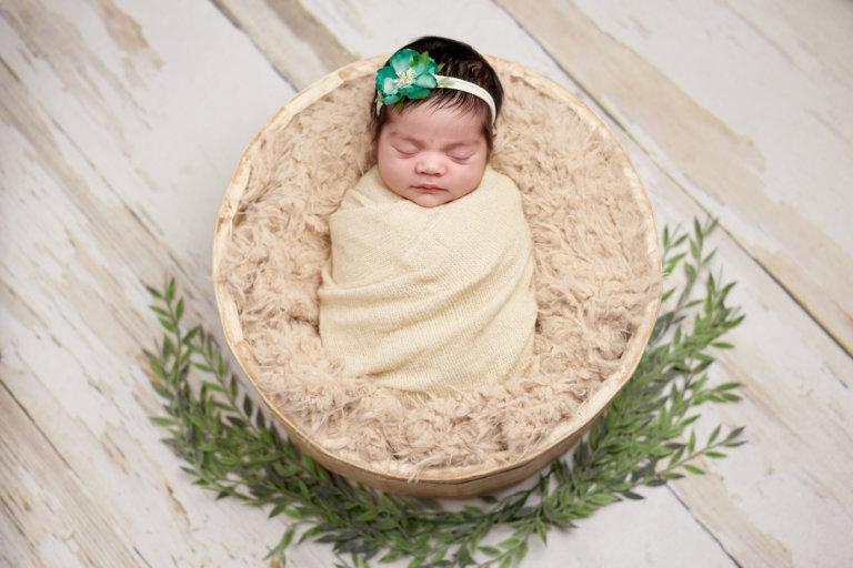 Elegant newborn baby photo with girl wrapped in soft blanket sitting in basket for girl in Philadelphia, Pennsylvania
